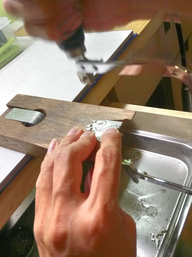 Hand sawing silver into a pendant